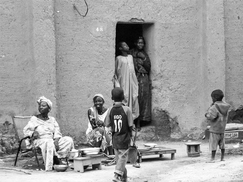 mujeres sentadas en la puerta de su casa de adobe djenne en su dia de mercado