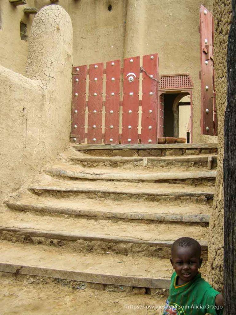 niño en la puerta de la mezquita djenne en su dia de mercado