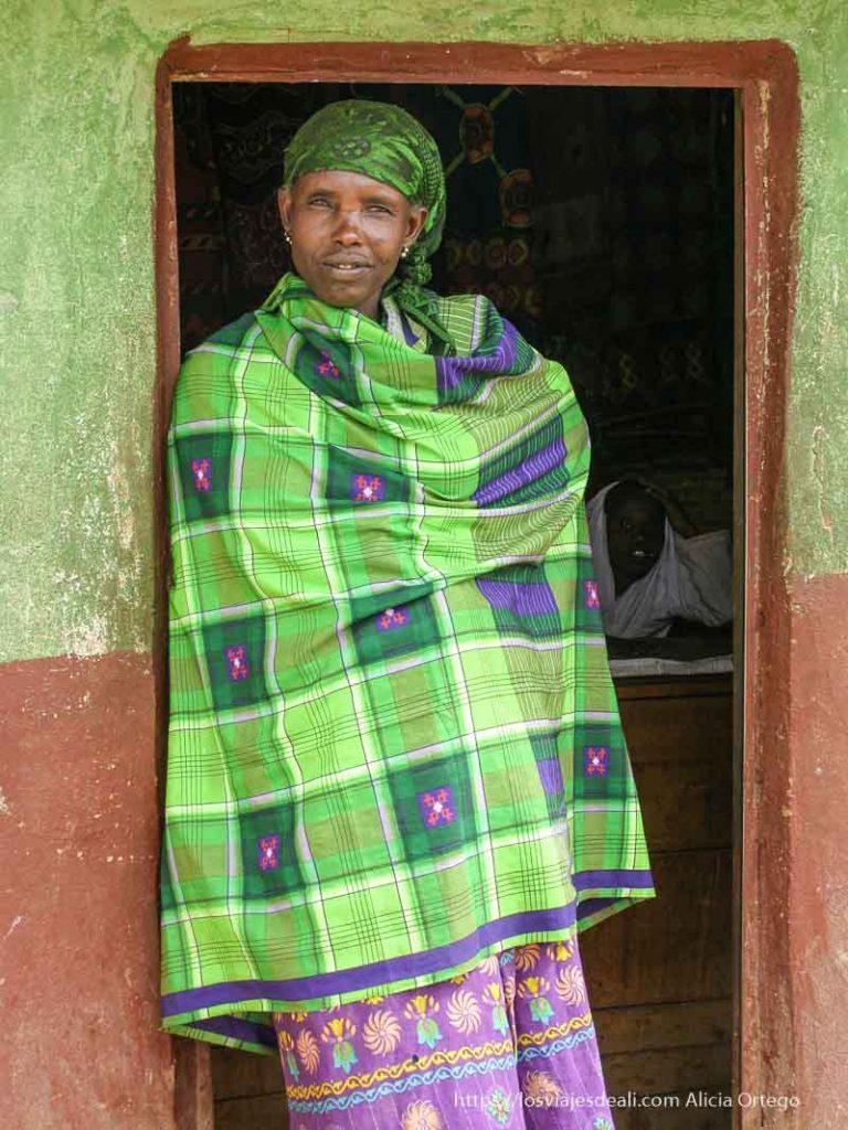 mujer apoyada en la puerta lleva una tela y turbante verde lima y la pared es del mismo color el sod