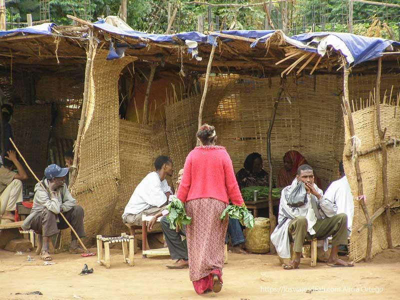 especie de choza con paredes de esterilla donde hay hombres y mujeres sentados en taburetes pequeños el sod