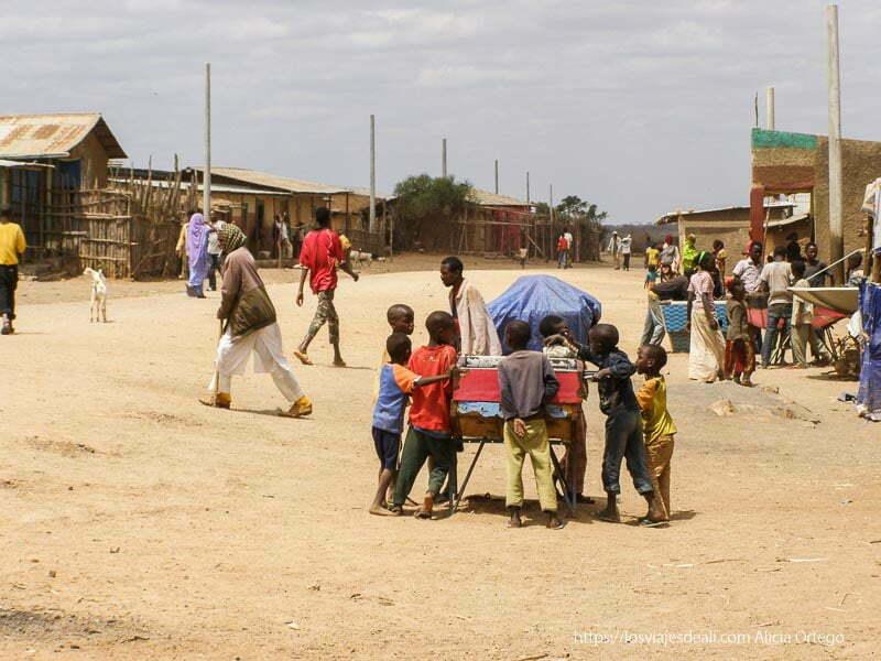 calle del pueblo con futbolín y niños jugando el sod