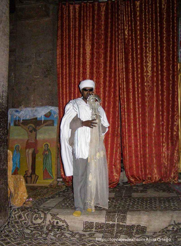 cura dentro de una de las iglesias lalibela mostrando una cruz y grandes cortinas rojas detrás