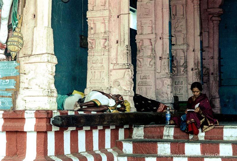 mujer leyendo y hombre recostado en un templo de kanchi tamil nadu