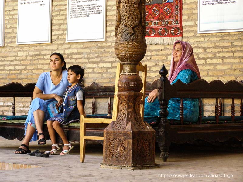 mujeres sentadas en bancos de madera en khiva