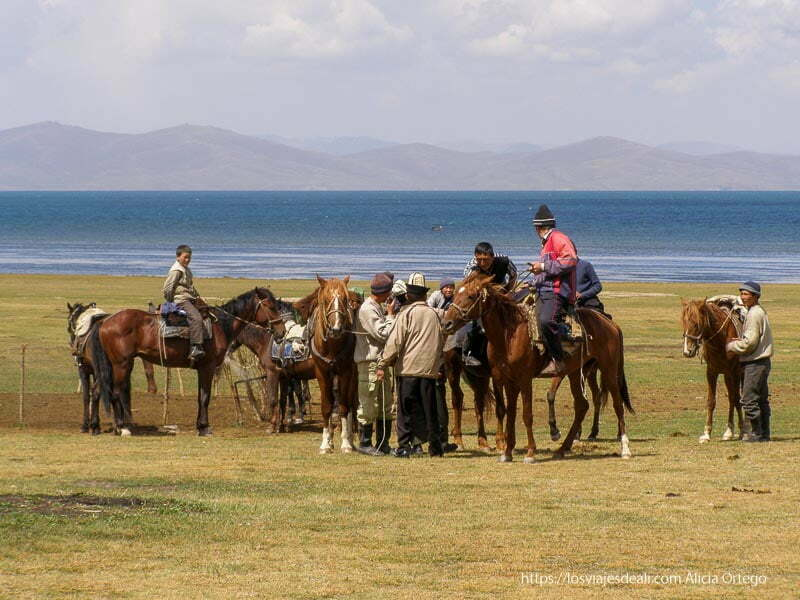 jinetes kirguises en sus caballos con el lago song kol detrás