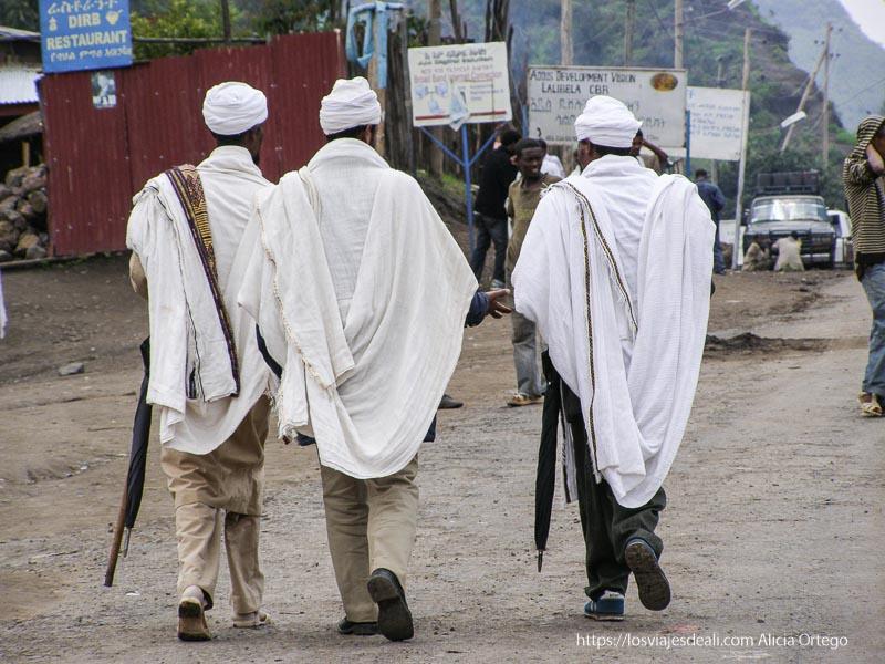 tres hombres caminando por lalibela con turbante y mantos blancos