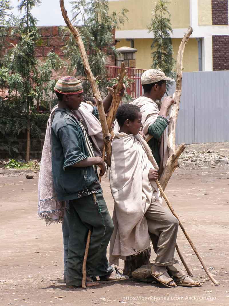 tres hombres sentados y apoyados en rama de árbol seco en lalibela