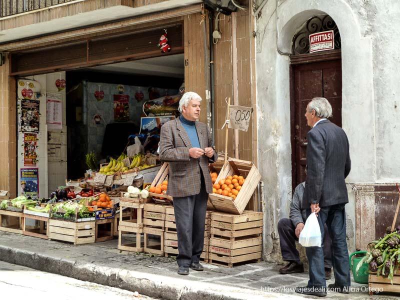 dos sicilianos hablando en puerta de frutería en monreale