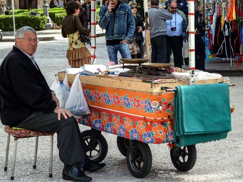 señor vendiendo almendras en monreale con carrito de colores