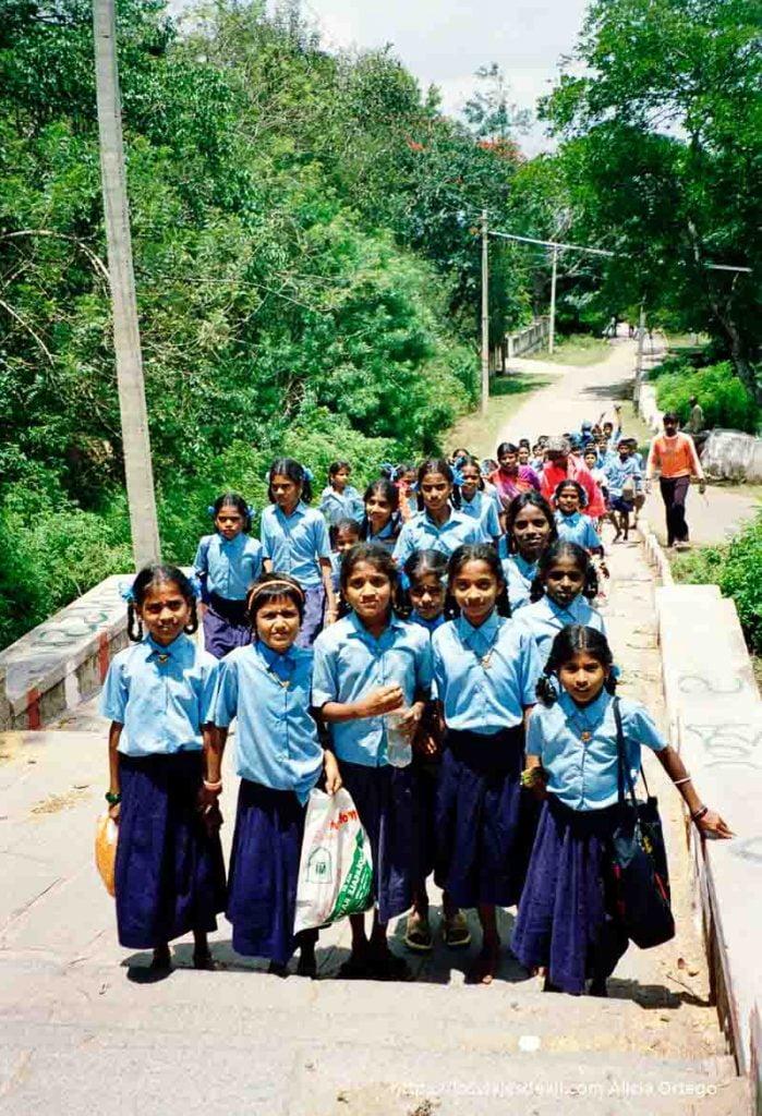 grupo de niñas con uniforme azul subiendo al templo de mysore