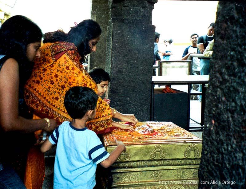 mujer y sus hijos poniendo ofrenda en altar con pies de plata en mysore