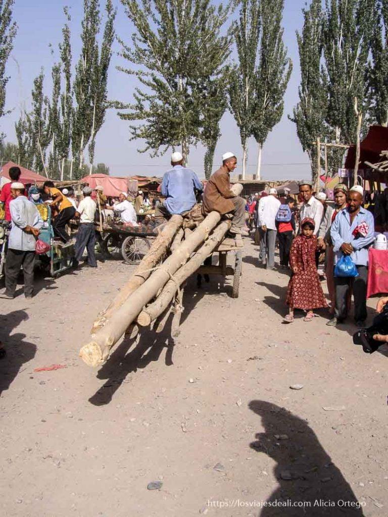 carro con enormes troncos entre la gente oasis de yarkand