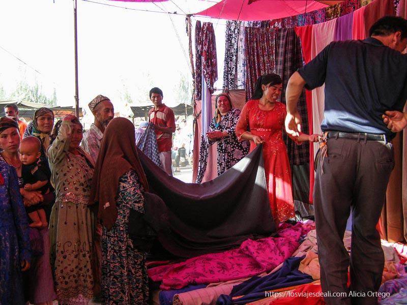 mujeres eligiendo telas en un puesto del mercado oasis de yarkand