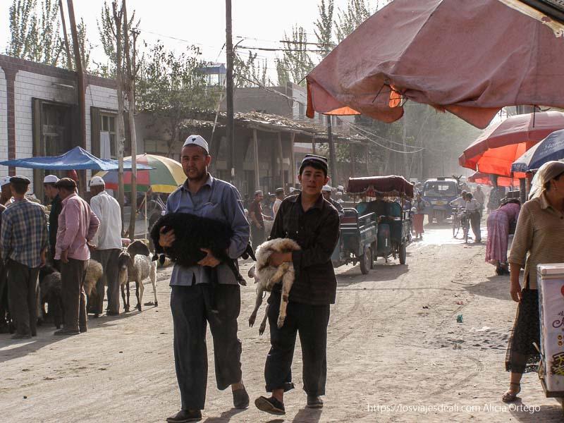 dos hombres llevando en brazos corderos en el mercado oasis de yarkand