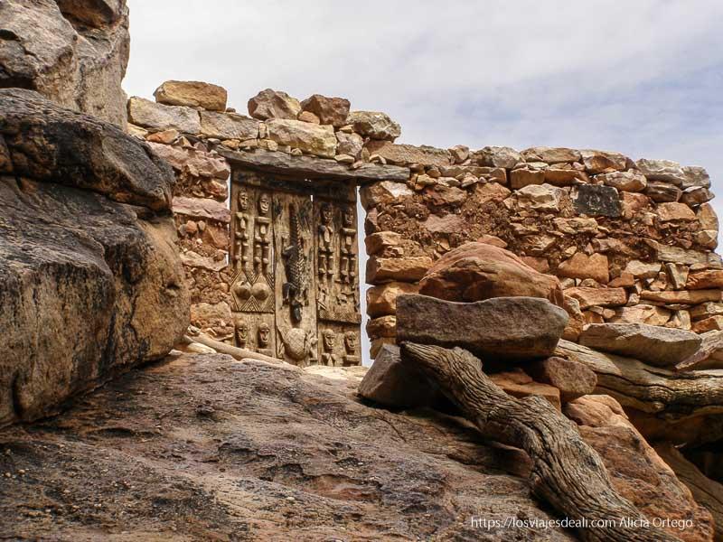 puerta decorada con cocodrilo, tortuga y ancestros en muro de piedra pais dogon
