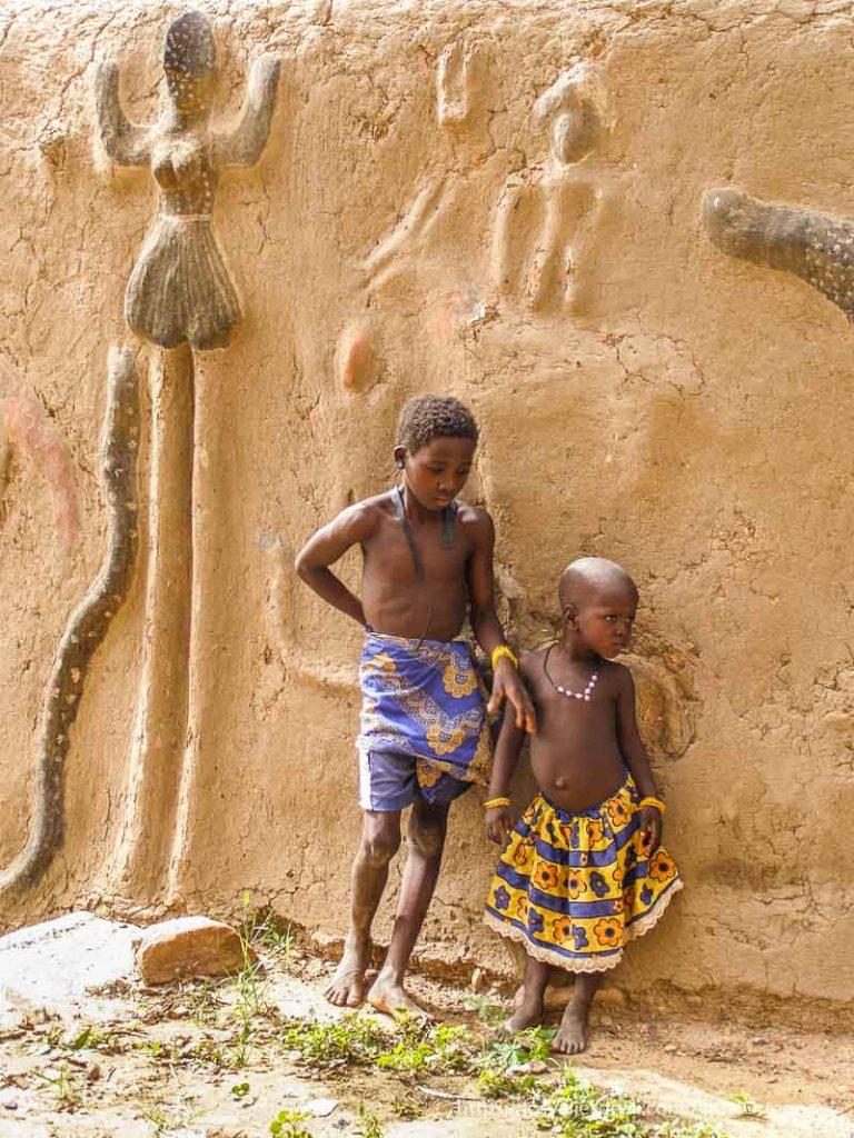 dos niñas junto a un muro donde hay figuras pintadas pais dogon