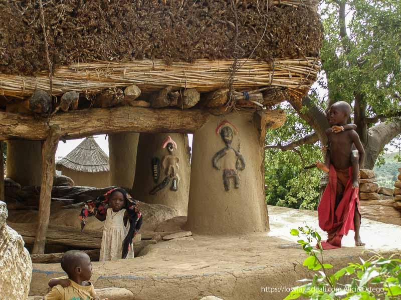 casa de la palabra con columnas con figuras de guerreros pintadas y niños pais dogon