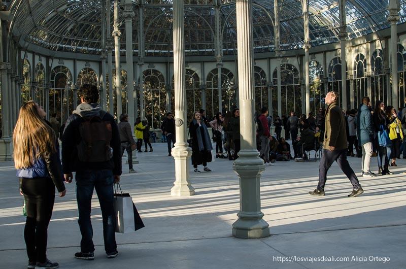 gente mirando la cúpula del palacio de cristal de el retiro