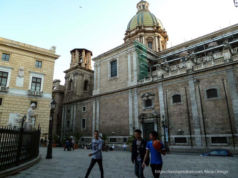 plaza con chavales y un palacio con cúpula de tejas verdes y amarillas palermo