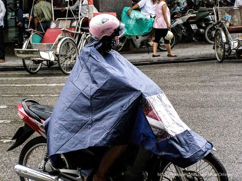 motorista tapada con capa de plástico en pleno chaparrón qué ver en hanoi