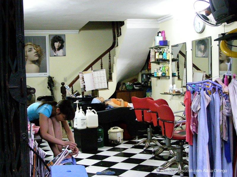 peluquería con mujer tumbada al fondo y otra pintándose las uñas de los pies qué ver en hanoi