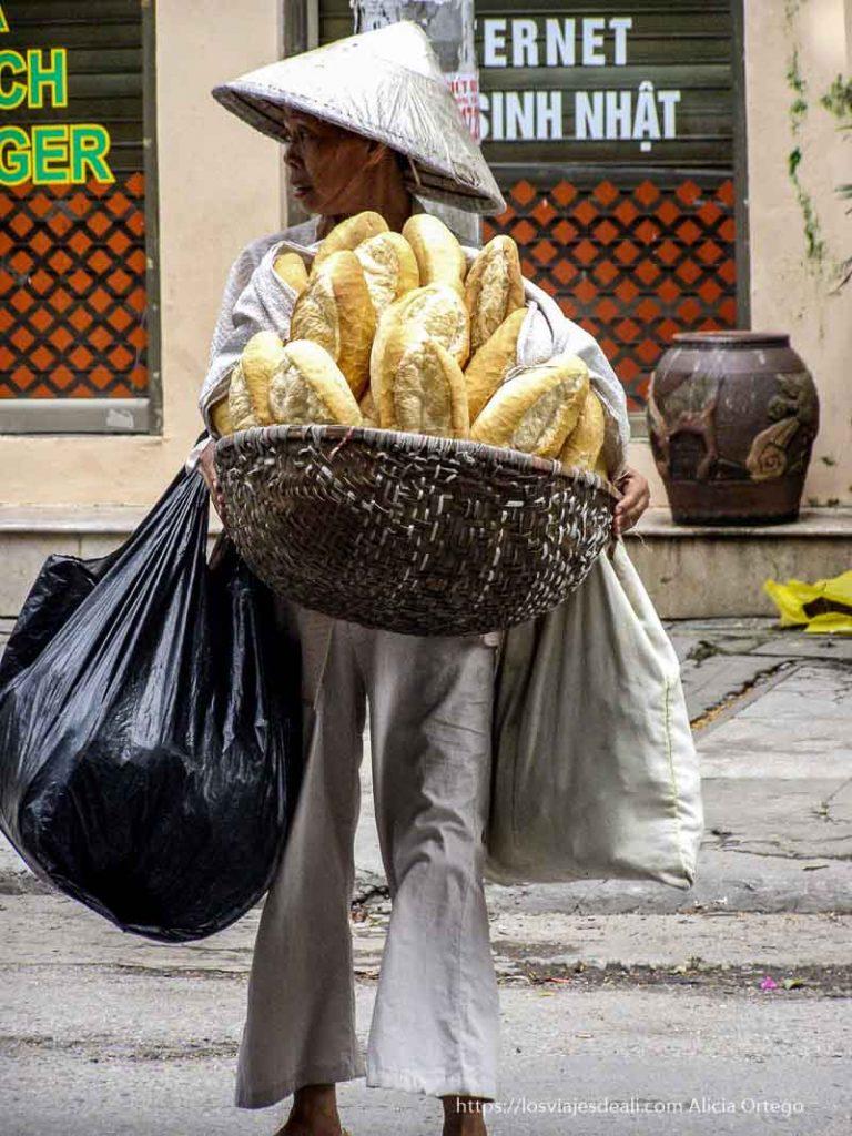 mujer mayor con típico sombrero cónico llevando cesta llena de barras de pan qué ver en hanoi