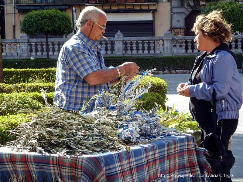 puesto de venta de ramas de olivo y señora comprando qué ver en palermo