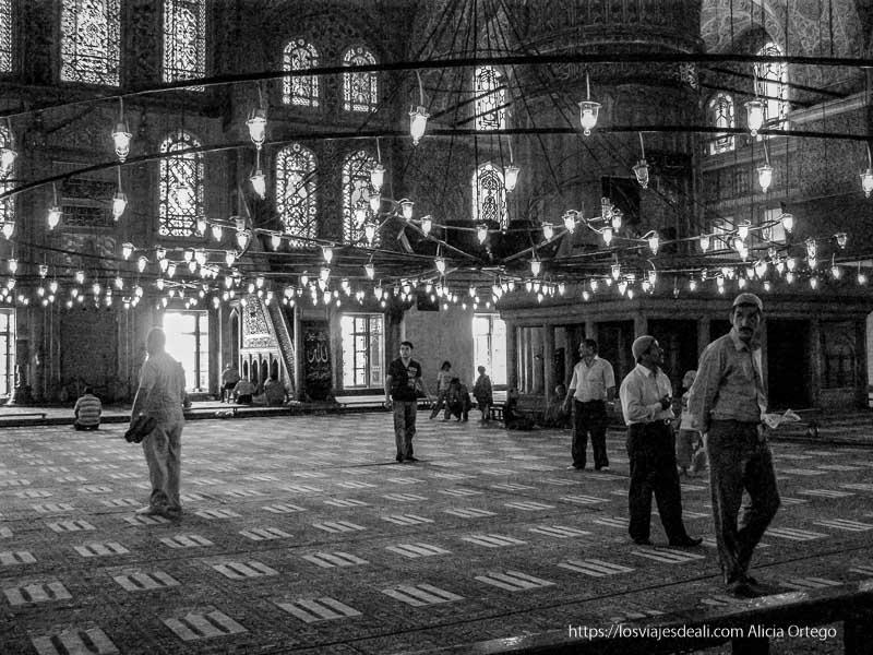 sala de oraciones de mezquita azul con lámparas y hombres visitándola qué ver en un día en estambul