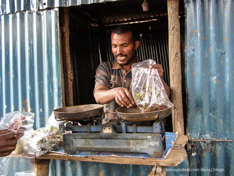 vendedor pesando bolsas de chat en antigua báscula sesión de chat