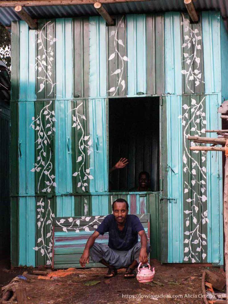 tienda de chapa pintada de verde con hojas y ramas y un hombre en cuclillas delante sesión de chat