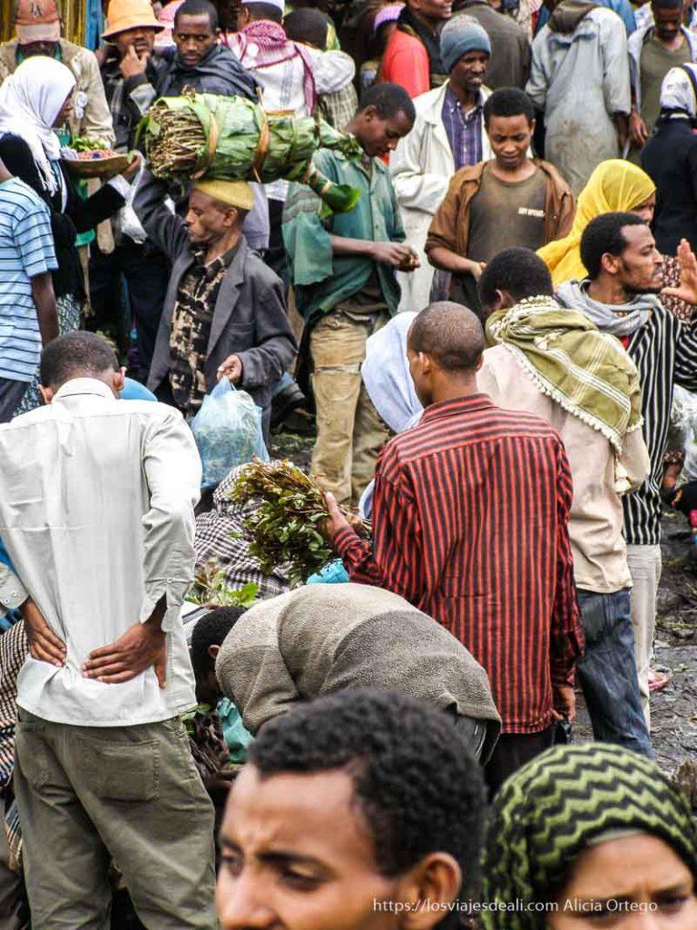 mercado de chat en addis abbeba lleno de gente con sus ramos y fardos
