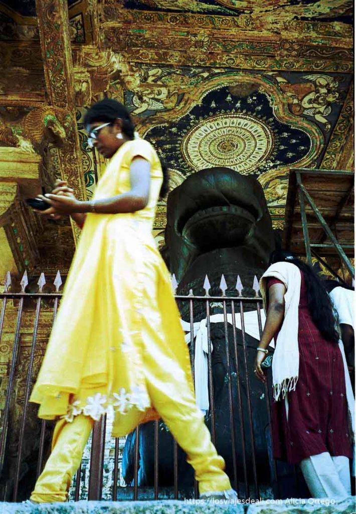 mujer con sari amarillo pasa delante del dios Nandi de tamil nadu a kerala