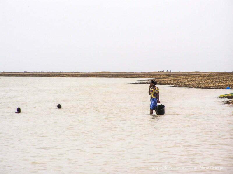 mujer entrando en el agua del níger con un cubo en la mano un sueño hecho realidad