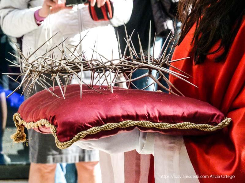 corona de espinas sobre cojín rojo llevada por una niña con capa roja Trapani en semana santa