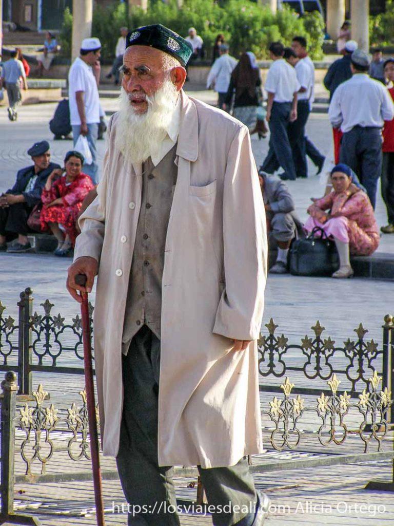 anciano con larga barba blanca, sombrero verde y guardapolvos beige kashgar en la ruta de la seda