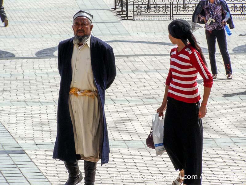 un hombre con botas de montar y abrigo largo en la plaza de kashgar en la ruta de la seda