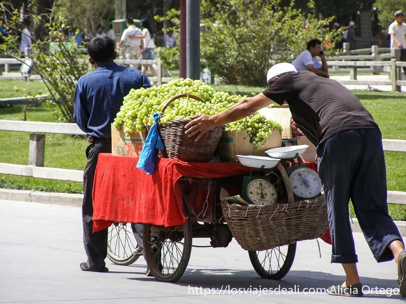 dos hombres empujando un carro lleno de uvas kashgar en la ruta de la seda
