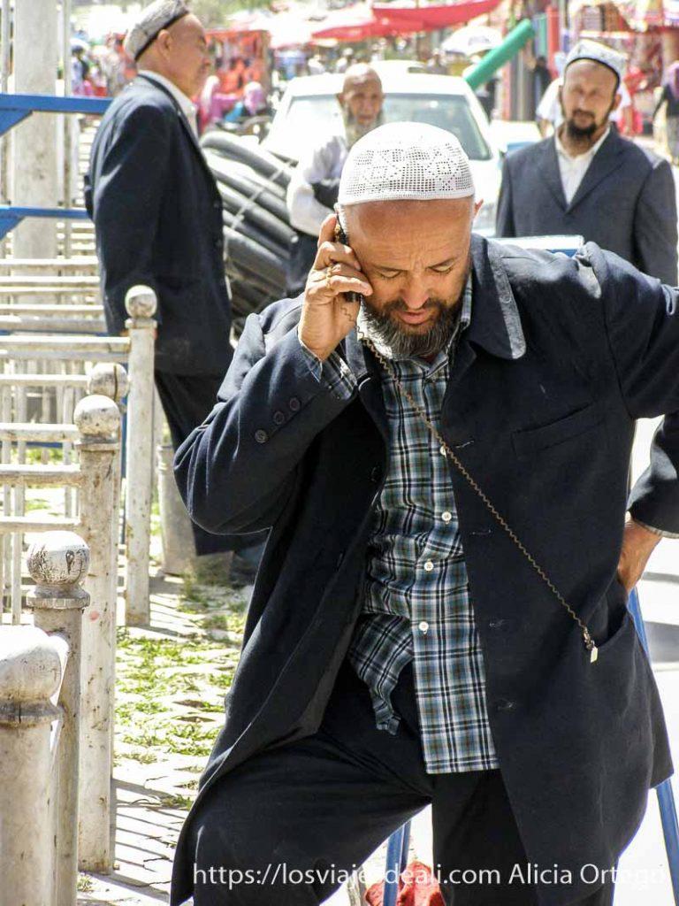 hombre hablando por el móvil sujeto con alambre al bolsillo de la chaqueta kashgar en la ruta de la seda