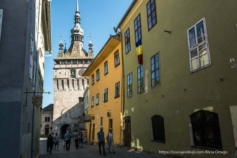 calle de sighisoara con casas de color verde y amarillo y al fondo la torre