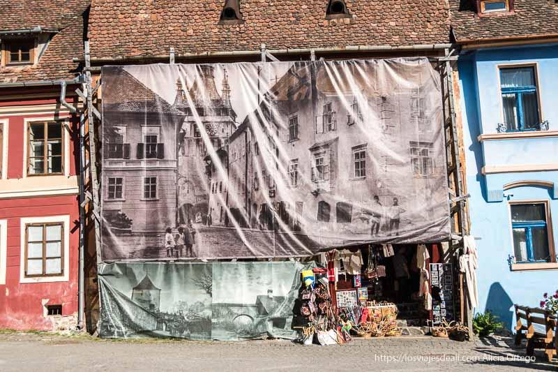 casa de plaza de sighisoara con gran cartel con foto antigua de la ciudad
