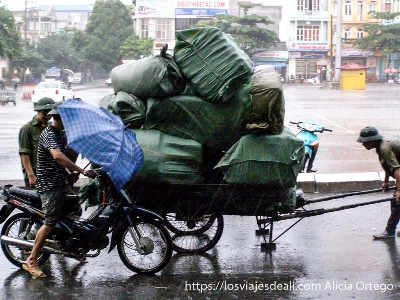 carro lleno de grandes bultos tirado por hombres en medio de la lluvia del monzón en el norte de vietnam