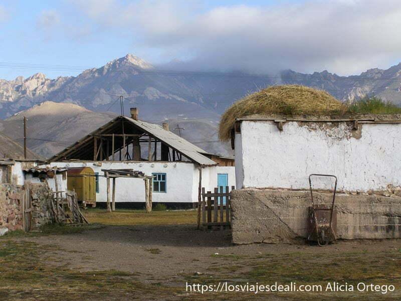 casas del pueblo con montañas al fondo y montones de paja en los tejados campo base del pico lenin