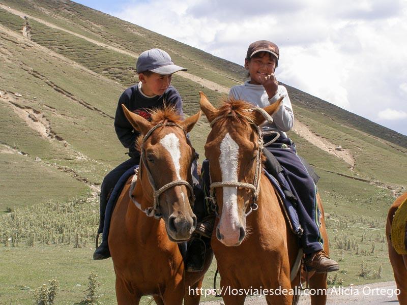 niños kirguises con gorra montados en sus caballos campo base del pico lenin