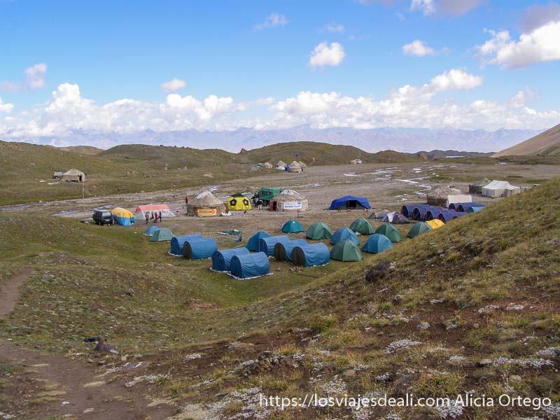 campo base del pico lenin con tiendas azules y verdes y las montañas alrededor