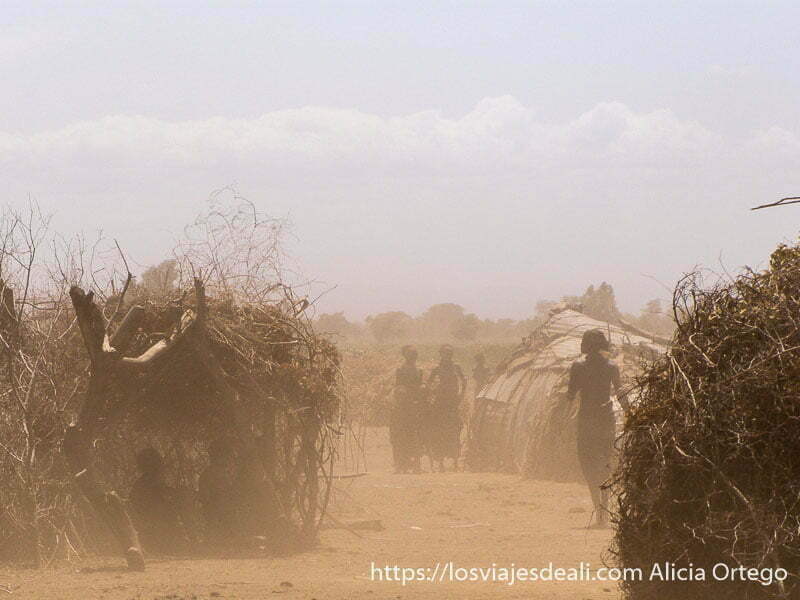 poblado de la tribu dasanech con mujeres andando entre las casas y mucho polvo