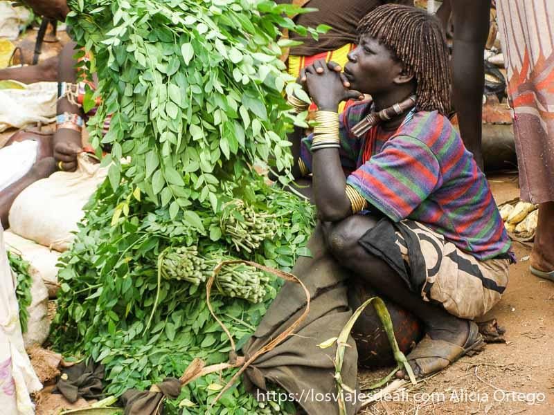 mujer en cuclillas con brazaletes, collar grande mercados del sur etíope