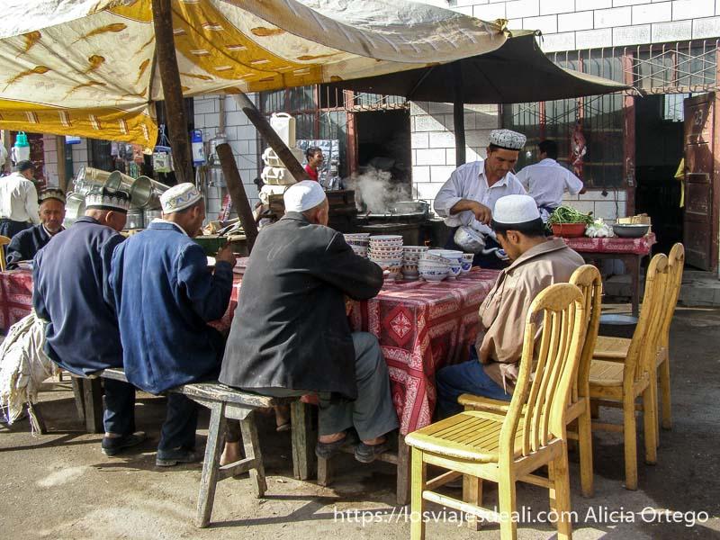 hombres comiendo en un puesto del mercado de Kashgar