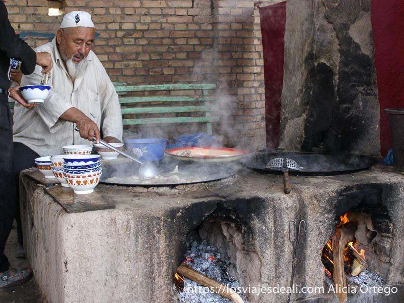 hombre cocinando arroz pilov en hornos de leña mercado de Kashgar