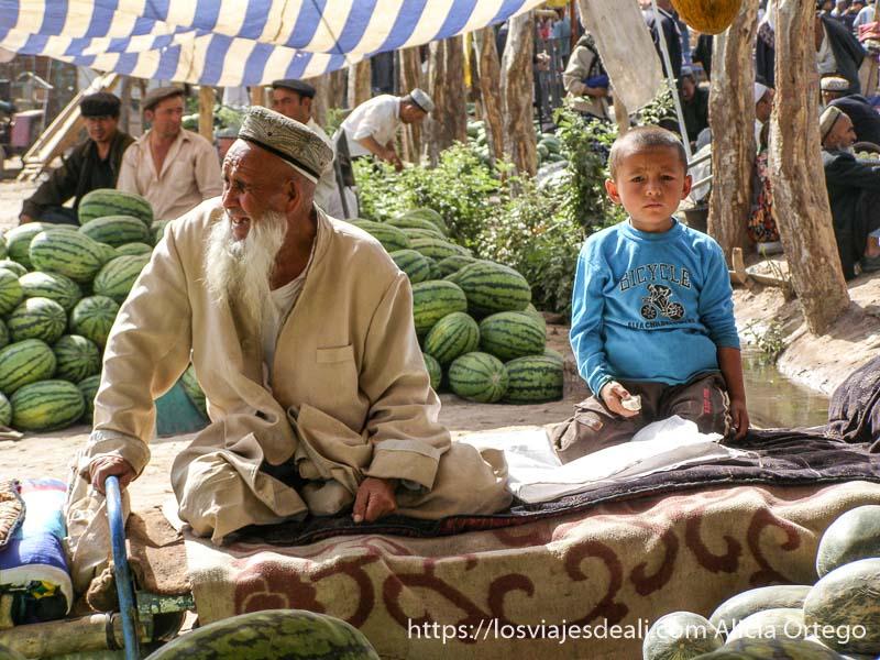 anciano y niño sentados entre melones en el mercado de Kashgar
