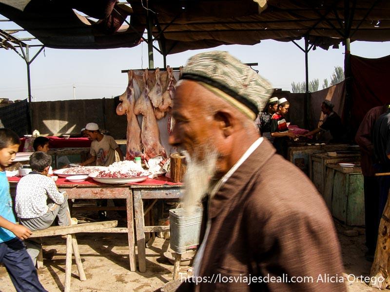 hombre mayor pasando delante de la cámara mercado de Kashgar